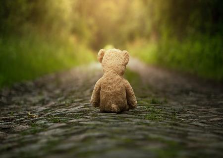 enfants: Ours en peluche solitaire sur la route Banque d'images