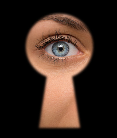 Close up of shocked female eye looking through a keyhole