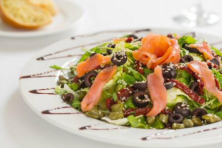 olives: Close up of fresh salmon salad with dried tomatoes, olives and sesame seed
