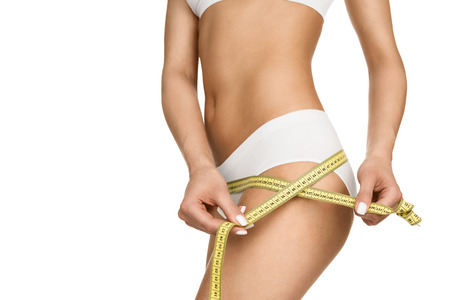 Close up of a slim woman measuring her hips isolated on white background