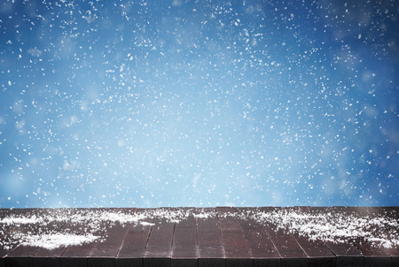 Close up of empty wooden table, desk and falling snow in the background with copy space