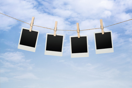 Close up of blank instant photos drying on the clothesline over sky background Banque d'images