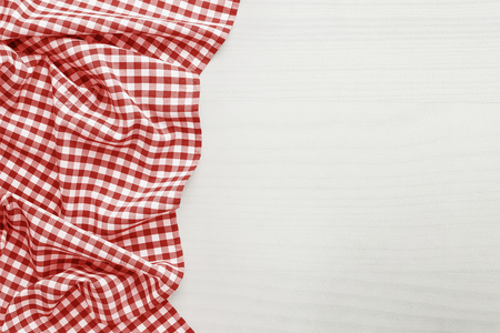 Food background, high angle view of white wooden table and red folded, checkered tablecloth white copy space Archivio Fotografico