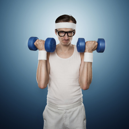 Funny sport nerd lifting weights isolated on blue background