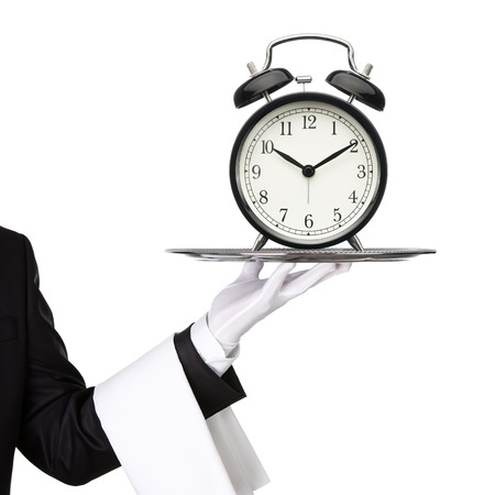 waiter tray: Waiter holding silver tray with an old clock isolated on white background Stock Photo