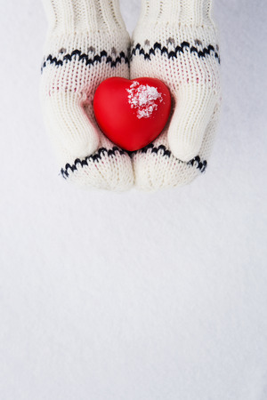 day care: Winter background, close up of little girls hands holding red rubber heart with copy space