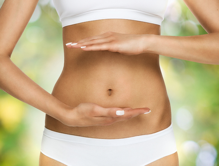 slim tummy: Pregnancy or diet concept, female hands protecting the stomach over nature background Stock Photo