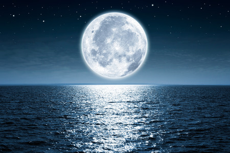 completos: La luna llena se levanta sobre el océano vacío en la noche con espacio de copia