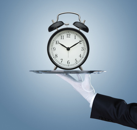 waiter tray: Waiter holding a silver tray with an old clock on it Stock Photo