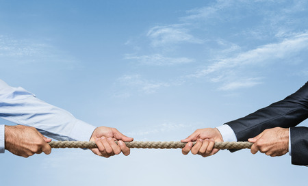 Tug war, two businessman pulling a rope in opposite directions over sky background with copy space