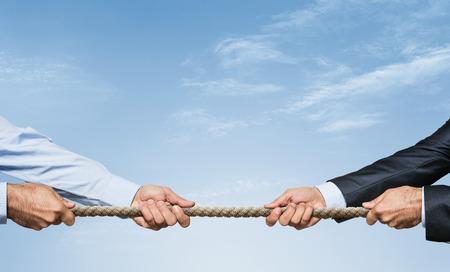 Schlepper Krieg, zwei Unternehmer, die ein Seil in entgegengesetzte Richtungen über Himmel Hintergrund mit Kopie Raum ziehen