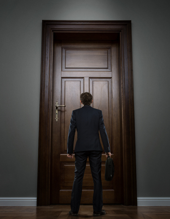 front office: Small young businessman standing in front of the boss office door Stock Photo