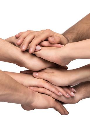 manos juntas: El trabajo en equipo de cerca de muchas manos humanas apiladas juntas aisladas sobre fondo blanco Foto de archivo