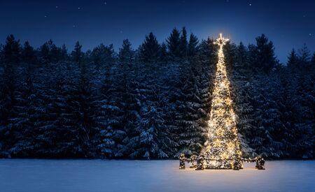 Albero di Natale illuminato in mezzo alla neve durante la notte con spazio di copia