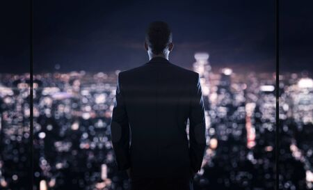 businessman in office: Close up of young successful businessman looking at the the city at night