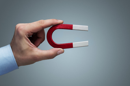 Male hand holding horseshoe magnet with copy space