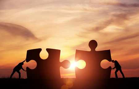 merge together: Teamwork concept. Two businessman connecting puzzle pieces togheter with copy space Stock Photo