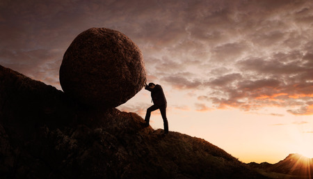 sisyphus: Business concept, Young businessman pushing large stone uphill with copy space