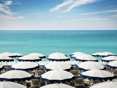 Summer background. Umbrellas on the Nice beach with copy space