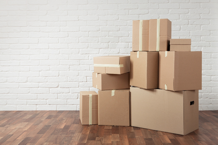 removals: Moving in. Stack of cardboard boxes in the empty room with copy space