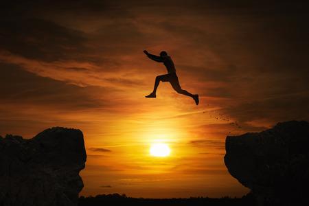 Silhouette eines Mannes über Abgrund bei Sonnenuntergang mit Kopie Raum springen Standard-Bild - 63299891