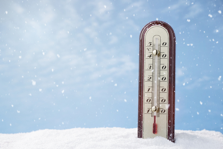 Close up of a thermometer in the snow with copy space