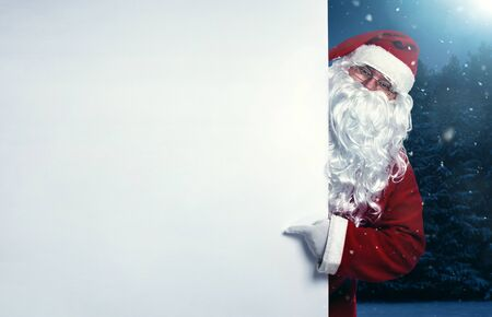 sheet of paper: Santa Claus pointing on blank white wall, advertisement banner with copy space Stock Photo