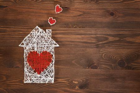 La douceur du foyer. Symbole de la maison à la main avec la forme de coeur sur fond en bois avec espace copie