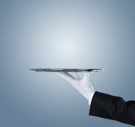 Waiter holding empty silver tray over blue background with copy space