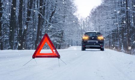 Destrozada coche y triángulo de emergencia en el camino cubierto de nieve en invierno