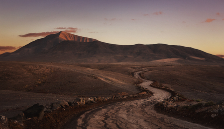 Empty desert road at the sunset with copy space. Papagayo beach, Lanzarote, Canary Island Stock Photo