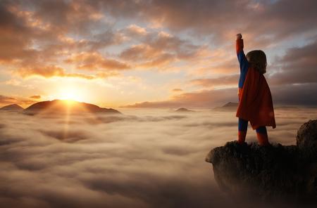 작은 소년 복사 공간이 일몰 산 위에 슈퍼 히어로처럼 행동