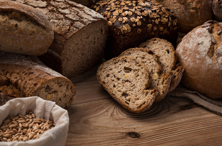 Many different handmade, freshly baked breads on wooden table with copy space Zdjęcie Seryjne