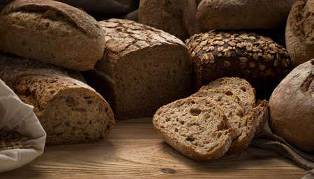 Viele verschiedene handgemachte, frisch gebackene Brote auf Holztisch mit Kopie Raum