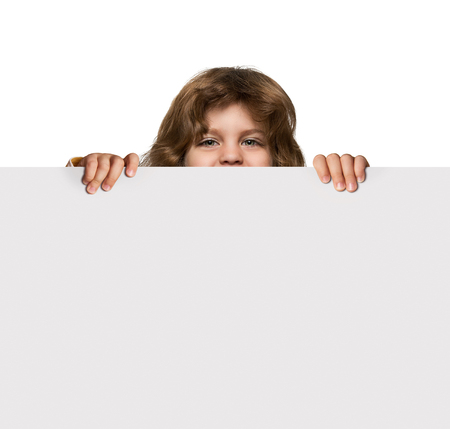 Happy little boy hiding behind blank advertising banner with copy space Stock Photo