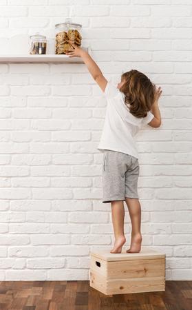 Cute little baby boy dotarcia do coockies na półce Zdjęcie Seryjne