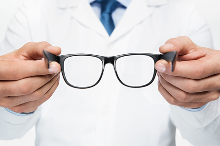 Close up of doctor oculist, optometrist holding new eyeglasses Lizenzfreie Bilder