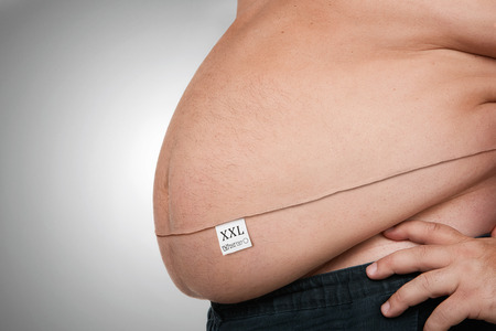 Fettleibigkeit Konzept, Nahaufnahme von Bauch Fett, Stich und Waschen Tag auf sie, isoliert auf grauem Hintergrund mit Kopie Raum