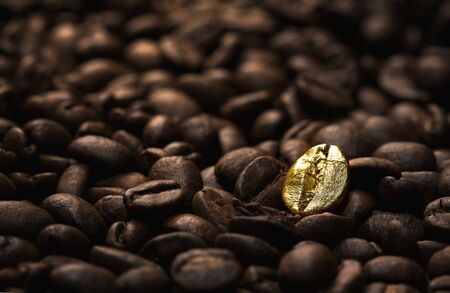 gold: Individuality, standing out  from a crowd concept, close up of a single bright, gold coffee bean over many dark ones with copy space