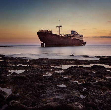 Schiffswrack am Sonnenuntergang auf einer Lanzarote Küste mit Kopie Raum
