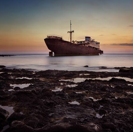 ocean waves: Shipwreck at the sunset on a Lanzarote coast with copy space Stock Photo