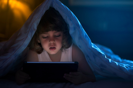 cover: Close up of little boy watching cartoons on the digital tablet at night with copy space