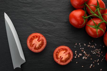 High Angle View von frisch gepflückt, juisy Tomaten auf dunklen Stein Hintergrund mit Kopie Raum