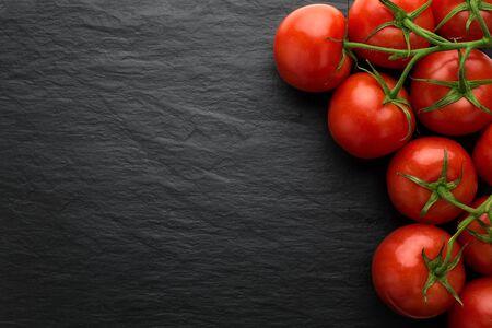 Nahaufnahme von frisch gepflückten Tomaten auf dunklen Stein Hintergrund mit Kopie Raum