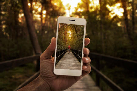 Travel concept, close up of a male hand photographing person in the forest Lizenzfreie Bilder