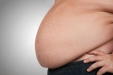 Obesity, close up of fat mans belly, isolated on gray background with copy space