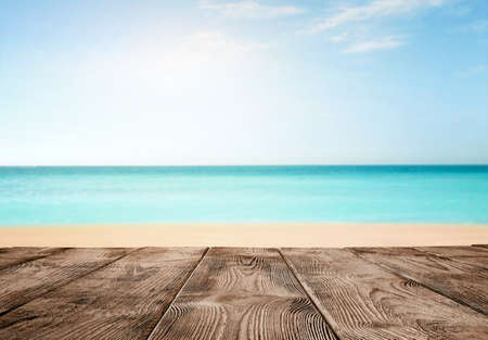 Summer background, close up of old empty wooden pier over the turquoise ocean with copy space