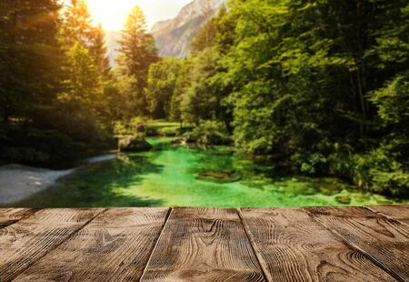 Old empty wooden pier or table over alps mountain river with copy space