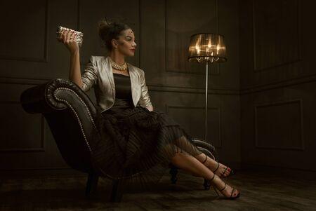 Fashion Porträt der eleganten Frau sitzt auf dem Stuhl mit Kopie Raum