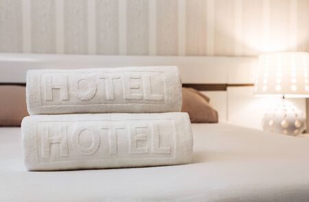 Close up of bath towels on the bed in the hotel room with copy space Standard-Bild